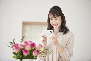 花をスマートフォンで撮影する女性の写真素材 [FYI04770221]