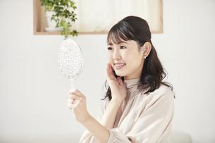 ソファに座り頬に触れながら鏡を見る女性の写真素材 [FYI04770222]