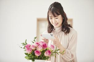 花をスマートフォンで撮影する女性の写真素材 [FYI04770225]