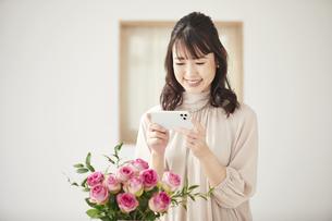 花をスマートフォンで撮影する女性の写真素材 [FYI04770229]