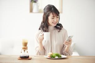 食事をしながらスマートフォンを見る女性の写真素材 [FYI04770230]