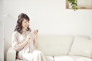 ソファに座りスマートフォンを見る女性の写真素材 [FYI04770232]
