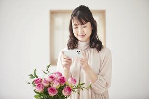 花をスマートフォンで撮影する女性の写真素材 [FYI04770233]