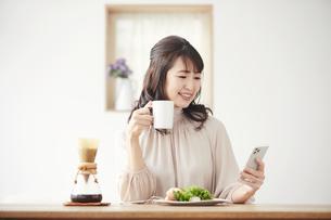 食事をしながらスマートフォンを見る女性の写真素材 [FYI04770234]