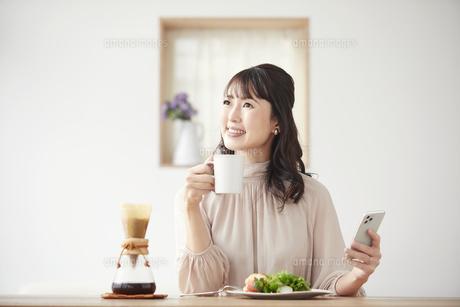 食事をしながらスマートフォンを持つ女性の写真素材 [FYI04770238]
