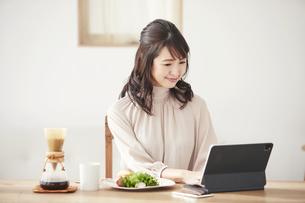食事をしながらタブレット端末を見る女性の写真素材 [FYI04770242]