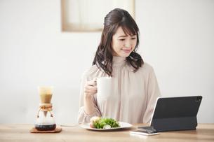 食事をしながらタブレット端末を見る女性の写真素材 [FYI04770246]