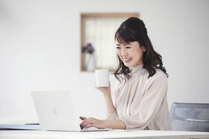 パソコンを見ながらオンライン会議をする女性の写真素材 [FYI04770247]