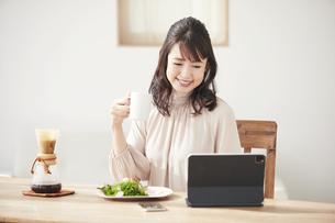食事をしながらタブレット端末を見る女性の写真素材 [FYI04770250]