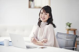 パソコンを開き仕事をするカメラ目線の女性の写真素材 [FYI04770251]
