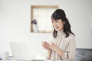 パソコンを見ながらオンライン会議をする女性の写真素材 [FYI04770256]