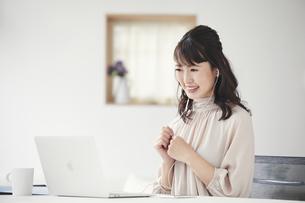 パソコンを見ながらオンライン会議をする女性の写真素材 [FYI04770257]