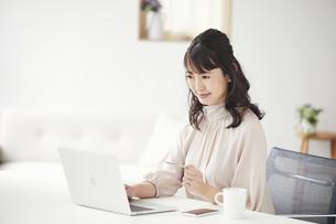 クレジットカードを持ちパソコンを見る女性の写真素材 [FYI04770261]