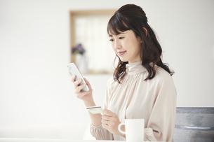 クレジットカードを持ちスマートフォンを見る女性の写真素材 [FYI04770262]