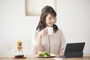 コーヒーを飲みながらタブレット端末を見る女性の写真素材 [FYI04770267]