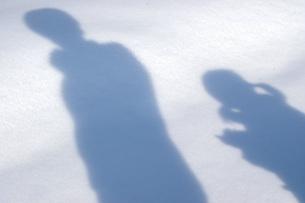 雪の上の親子のシルエットの写真素材 [FYI04770368]