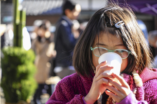 初詣で甘酒を飲む女の子の写真素材 [FYI04770423]