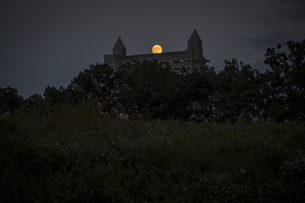 夕闇のマンション越しに浮かぶ満月の写真素材 [FYI04770648]