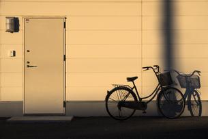 壁際で夕陽に浮かぶ自転車のシルエットの写真素材 [FYI04770673]