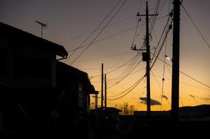 明かりが灯る電柱とシルエットの家並みの写真素材 [FYI04770680]