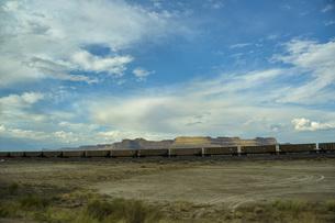 不毛の大地を貨物列車が走る風景の写真素材 [FYI04771110]