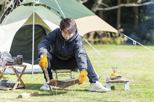 薪をくべる男性の写真素材 [FYI04771323]