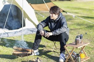 キャンプ場でくつろぐ男性の写真素材 [FYI04771362]