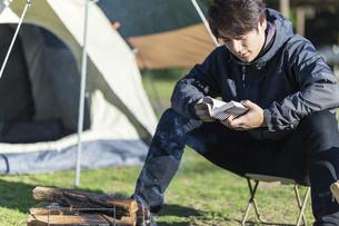 キャンプ場でくつろぐ男性の写真素材 [FYI04771364]