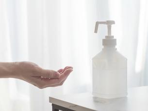 アルコール消毒スプレーで手を消毒する様子。新型コロナウイルス・COVID-19対策。の写真素材 [FYI04771394]