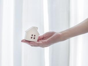 手と家。不動産・家庭・家族・生活などのイメージ。の写真素材 [FYI04771449]