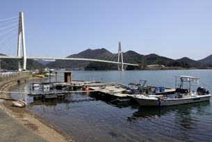 舞鶴湾に架かる舞鶴クレインブリッジと漁船の写真素材 [FYI04771496]