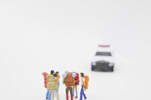 話し合う旅行者を規制するパトカーのミニチュア の写真素材 [FYI04771722]