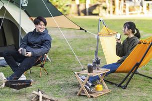 キャンプ場で会話をする男女の写真素材 [FYI04771922]