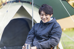 キャンプ場でくつろぐ男性の写真素材 [FYI04771925]