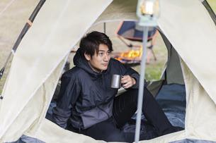 テントでくつろぐ男性の写真素材 [FYI04771952]