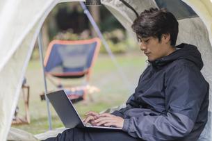 テントでくつろぐ男性の写真素材 [FYI04771956]