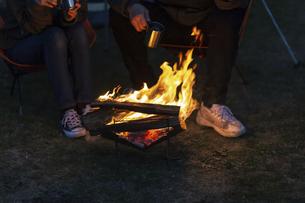 焚き火にあたる男女の足元の写真素材 [FYI04771960]