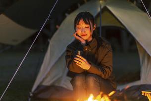 焚き火にあたる女性の写真素材 [FYI04771962]