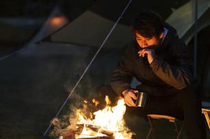 焚き火にあたる男性の写真素材 [FYI04771964]
