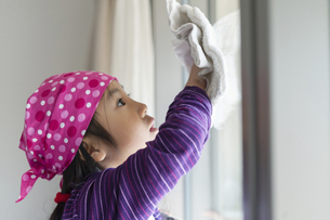 窓拭きをする女の子の写真素材 [FYI04772963]