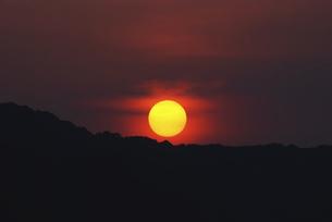 沈む太陽と山並みの写真素材 [FYI04772983]