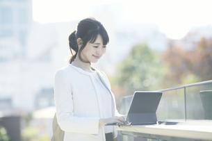 タブレットPCを持ち屋外を歩くビジネスウーマンの写真素材 [FYI04773086]