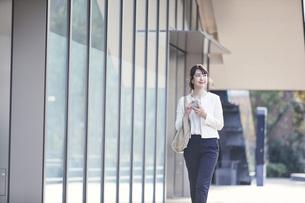 スマホを持ち屋外を歩くビジネスウーマンの写真素材 [FYI04773088]