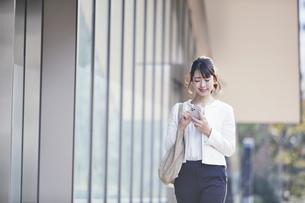 スマホを持ち屋外を歩くビジネスウーマンの写真素材 [FYI04773091]