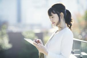 タブレットPCを持ち屋外を歩くビジネスウーマンの写真素材 [FYI04773092]
