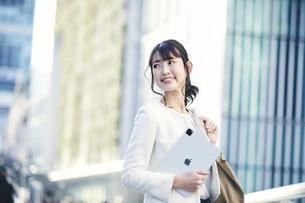 タブレットPCを持ち屋外を歩くビジネスウーマンの写真素材 [FYI04773115]