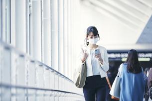 マスクをしてスマホを持つビジネスウーマンの写真素材 [FYI04773148]