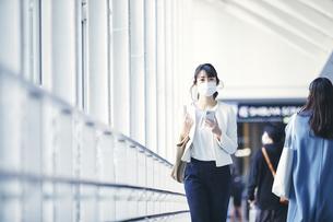 マスクをしてスマホを持つビジネスウーマンの写真素材 [FYI04773151]