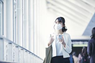 マスクをしてスマホを持つビジネスウーマンの写真素材 [FYI04773153]