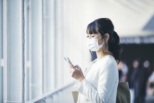 マスクをしてスマホを持つビジネスウーマンの写真素材 [FYI04773158]